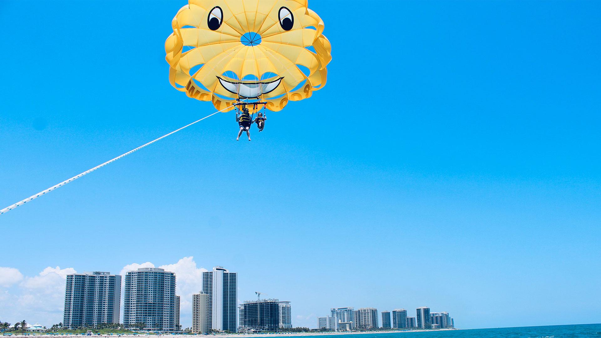 Couple parasailing along the palm beach coast